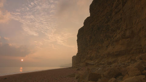 Timelapse - sun sets next to large towering cliffs by the sea Live Action
