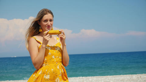Beautiful young woman in yellow summer dress eating corn on the beach. Summer Live Action