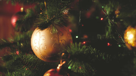 Closeup toned video of balls, garlands and lights hanging on Christmas tree on Live Action