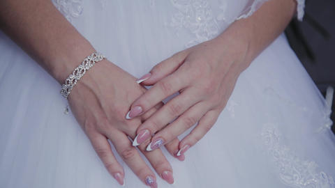 Bride's morning. Hands of a bride close-up lie on a white wedding dress Live Action