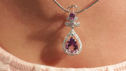 A man touches a silver pendant with a magenta diamond on a beautiful female neck Live Action