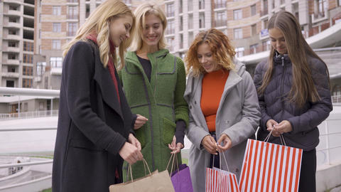 Four happy beautiful girls with shopping bags enjoying their purchases and Live Action