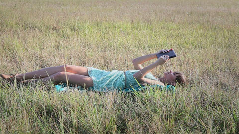 Young woman browsing in Internet with tablet lying on the grass Footage