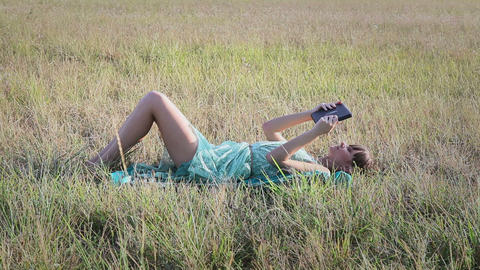 Young woman browsing in Internet with tablet lying on the... Stock Video Footage