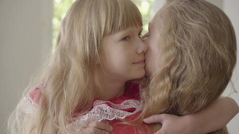 Cute little caucasian girl kissing caucasian woman on the cheek. Daughter Footage