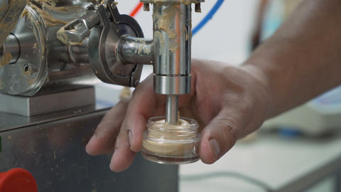Close look of machine filling small jar and Scientist measuring it on electronic Live Action