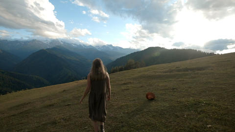Hipster millennial young beautiful girl steps on green grass in the mountains Footage