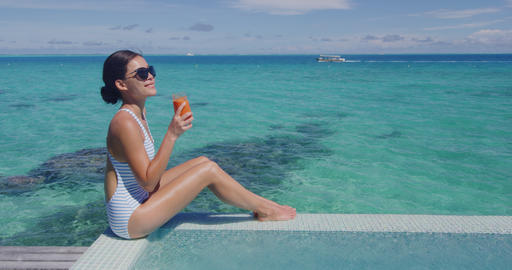 Healthy juice detox happy woman drinking carrot juicing smoothie glass at pool Footage