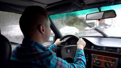 A young man is driving a car. Rainy weather. A view of a man from behind from Live Action