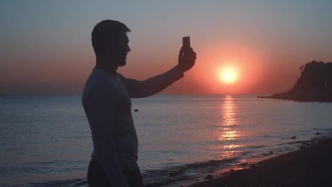 A young man stands on the shore against the backdrop of a sea sunset. Man makes Footage