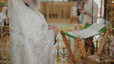 An old priest stands at the altar and reads a prayer Live Action