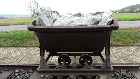 Old mining trolley minecart loaded with stones stands on rails Live Action