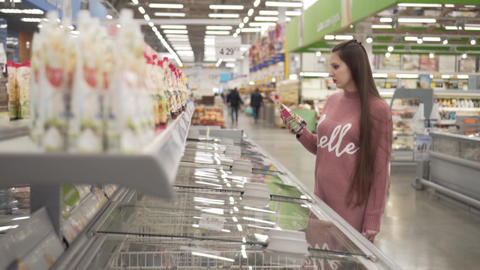 A young woman chooses products in the supermarket Live Action