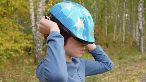 Teenager boy putting bicycle helmet on head in autumn park. Handsome boy wearing Live Action
