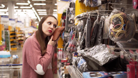 A young woman chooses a pillow for a car in a supermarket Live Action