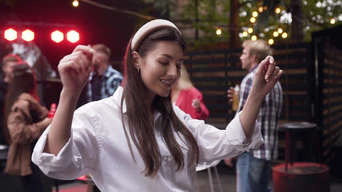 Attractive smiling young lady with long hair dancing with raised hands on camera Footage