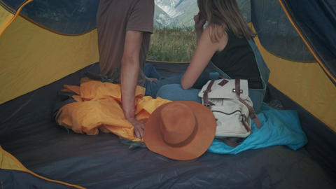 Couple of man and woman travelers in a tent. Hold on with little fingers, make Footage