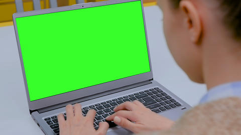 Woman typing on laptop computer keyboard with blank green screen in cafe Footage