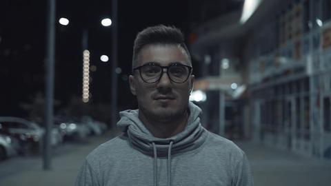 A happy and handsome guy with glasses looks into the frame and smiles, located Live Action