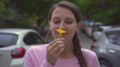 A beautiful girl with a scythe sniffs a yellow flower and puts it behind her ear Live Action