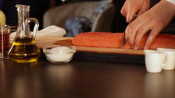 The chef cuts a big piece of raw salmon fillet.High protein foods Live Action