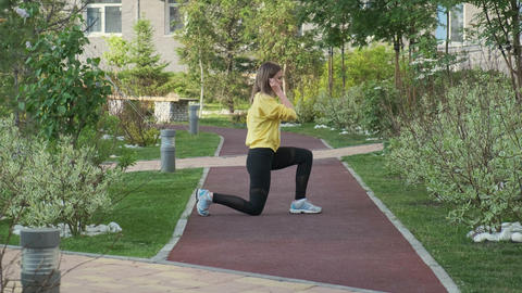 Young sporty woman exercises on street Live Action