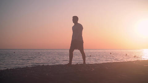 A young man walks along the shore against the backdrop of a sunset. A man walks Live Action