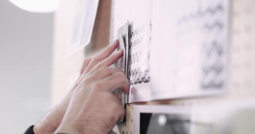 Closeup of fashion designer selecting fabrics for designs Footage