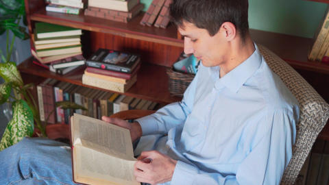 A young man reads a book while sitting in the home library, a man in a blue Footage