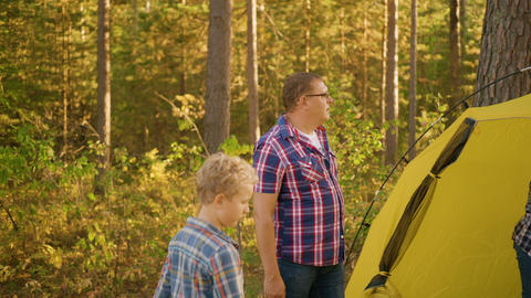 Family with one child near yellow tent in beautiful forest Live Action