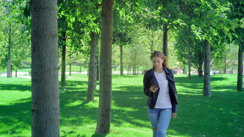 Young beautiful girl is walking in the park with a smartphone. Reads the message Live Action