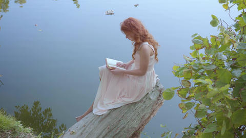 Young charming girl with long red hair in light pink dress is reading poetry at Live Action