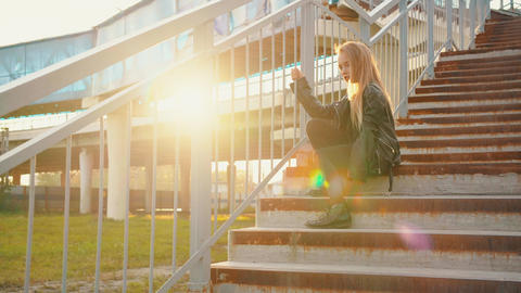 Teenager girl in black leather jacket sitting on stairs on sunflare background Footage
