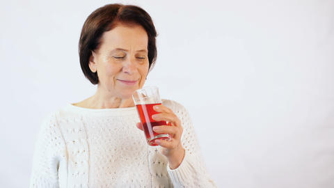Elderly woman drinking red juice Footage
