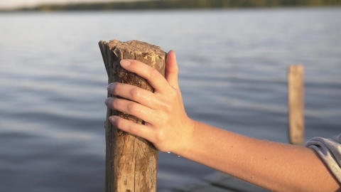 Water Drops from Female Hand on Wooden Jetty Pole Summertime - Natural Footage