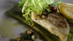 Close-up of grilled pike perch fillet with asparagus and lemon Live Action