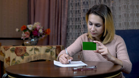 Girl with a credit card and documents. Fills the card data on a piece of paper Live Action