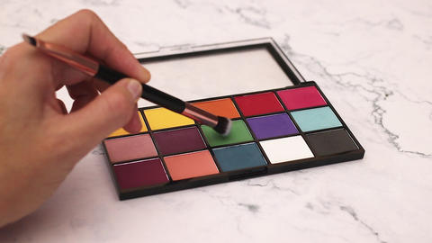 Woman hold eye shadow palette and smear shadow with make up brush Footage