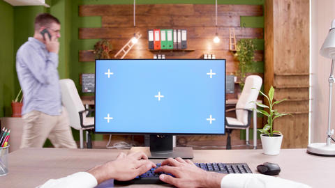 POV of man typing on mock-up PC in modern workplace Live Action