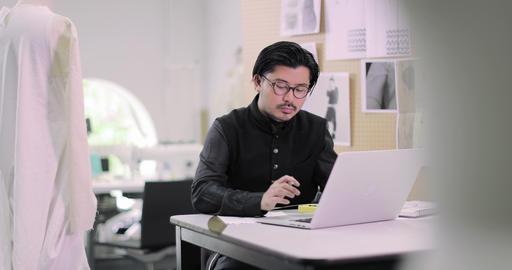 Fashion designer working on pattern with laptop Footage