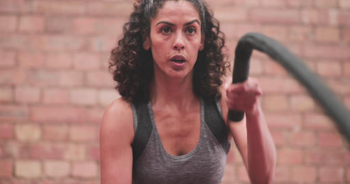 Closeup mid adult female working out with battle ropes Live Action