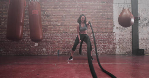 Mid adult female working out with battle ropes Live Action