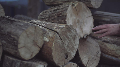 Man's hand touches the oak firewood blocks stored up for winter. Man's hand Live Action