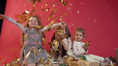 Three beautiful cheerful model kids throwing up and making golden confetti rain Footage