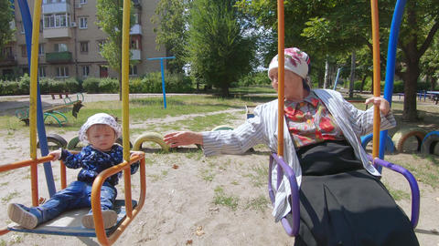 Grandmother with a grandson on a swing Footage