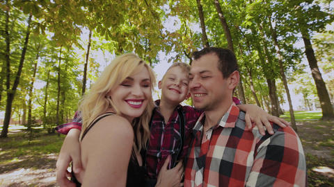Happy cheerful family hugging and smiling by the tree in the park Footage