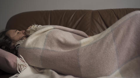Sick young caucasian woman coughing while lying under blanket at home. The child Live Action