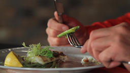A man eats blanched asparagus and grilled fillet of pike perch, served with Live Action