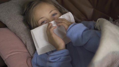 Close-up of sick caucasian girl sneezing. Sad child lying under blanket at home Live Action