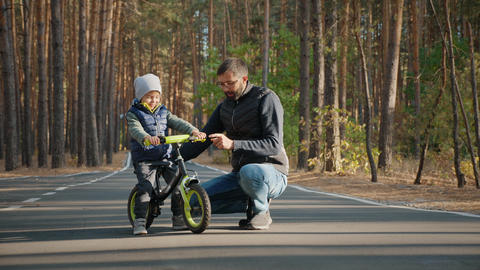 Young father teaches little son to ride a balance bike Footage